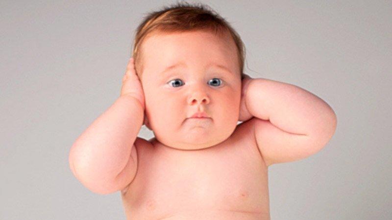 un bébé qui se bouche les oreilles